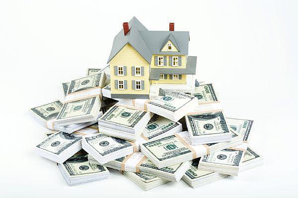 US dollars beneath a model house